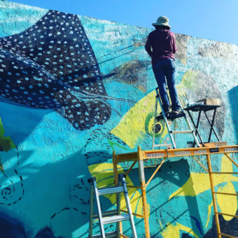 mural artist painting large scale mural spotted eagle ray manta ray large flounder fish