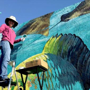 Mural artist Georgeta Fondos painting her aquatic mural depicting the Blue Heron Bridge's Snorkeling Trail