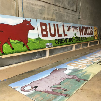 Mural artist Georgeta Fondos painting mural bull of the woods, mural on wood panels, a mural for the Coral Springs historic covered bridge, the bull of the woods mural, chewing tobacco logo